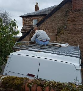 Solar panel being secured onto the roof rack